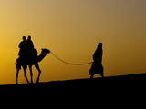 A Man Leads a Camel Along the Top of a Sand Dune in North West India Photographic Print by Kenneth Ginn