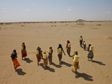 Gabra Women Carrying Heavy Jerry Cans Filled with Murky Water Photographic Print by Lynn Johnson