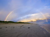 A Rainbow Crests a Storm Front over a Wide Deserted Beach at Twilight Photographic Print by Jason Edwards