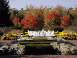 A Bubbling Fountain Surrounded by Plants and Colorful Trees Photographic Print by Paul Daimien