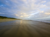 A Storm Surge Wets the Sand on a Wide Empty Beach at Sunset Photographic Print by Jason Edwards