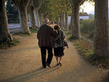 An Elderly Couple Walking Along a Tree-Lined Dirt Road Photographic Print by Tino Soriano