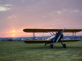 A Stearman Biplane on a Grass Airfield at Dawn Fotografiskt tryck av Pete Ryan