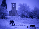 A Man Rolls a Ball of Snow Near the Church in Porqueres Photographic Print by Tino Soriano