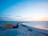 A Solo Camper Watches the Sunset from a Tiny Island Far Out to Sea Photographic Print by Ben Horton