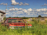 An Abandoned Red Car from the 1970S Sits in a Field Fotografiskt tryck av Pete Ryan