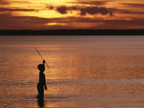 Young Boy Spear Fishing at Sunset in the Mouth of the Kikori River Delta, Papua New Guinea Photographic Print by Gerry Ellis