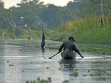 A Yanayacu Indian Fisherman Floats His Canoe in the Yanayacu River Photographic Print by Gordon Wiltsie