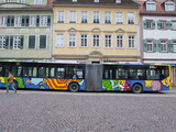 A Painted Double Long Bus in a Square in Heidelberg Photographic Print by Greg Dale