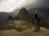 A Trekker Gazes across the Ruins of Machu Picchu to the Huayna Picchu Photographic Print by Aaron Huey