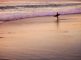 A Surfer Heads into the Waves Just as the Sun Is Setting Photographic Print by Ben Horton