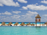 The Caribbean Sea, Tiki Huts and a Lifeguard Stand from a Resort Pool Fotografisk tryk af Mike Theiss