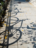 Shadows of Bicycles Cast on a Side Walk Photographic Print by Brian Gordon Green