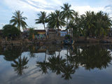 Palm Trees and Village Houses Casting Reflections in Water Photographic Print by Karen Kasmauski