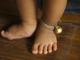 Vietnamese Infant's Feet with a Bell around the Ankle Photographic Print by Karen Kasmauski