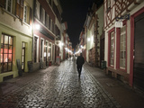 A Man Walks Down a Cobbled Street at Night Photographic Print by Greg Dale