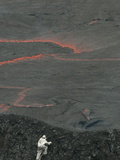 A Volcanologist, Wearing a Thermal Suit, Approaches an Active Lava Lake Photographic Print by Peter Carsten