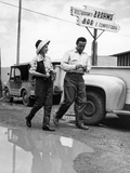 A Man and Woman Dodge a Puddle in the Street Photographic Print by Thomas J. Abercrombie
