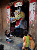 A Dragon Emerges from a Dragon Maker's Shop to Scare Children Lámina fotográfica por O. Louis Mazzatenta
