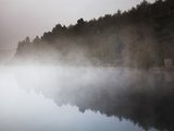 Fog Hovers over a Forest-Lined Lake at Dawn Photographic Print by Nigel Hicks