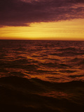 A Dramatic Sky Casts a Red Glow over Waves on Lake Michigan Photographic Print by Paul Damien