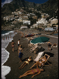 Sunbathers Lounge on a Pebbled Beach by Whitewashed Houses on a Cliff Photographic Print by Luis Marden