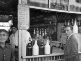 A Man Stands at the Edge of a Bar Surrounded by Bottles Photographic Print by Maynard Owen Williams