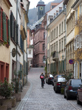 A Woman Rides a Bike Up a Cobbled Street in the Morning Reproduction photographique par Greg Dale