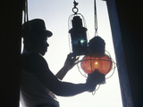 A Man Handles Red and Green Lanterns Hanging Near a Doorway Photographic Print by Luis Marden