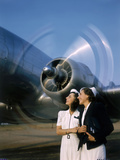 Two Young Women Stand Near a Turning Aircraft Propeller Photographic Print by Luis Marden