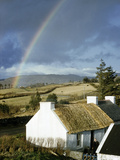 A Rainbow Arches over a Thatched White Cottage and Nearby Fields Photographic Print by Robert Sisson