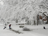 A Man Shoveling a Path in the Snow as His Pet Dog Relaxes Photographic Print by Karen Kasmauski