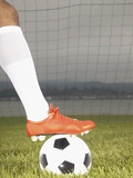 View of a football players foot on a soccer ball Photographic Print