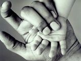 Hand of a black man and hand of a white baby Photographic Print by Nikos 