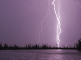 Lightning Striking near Lake Photographic Print by Mike Theiss
