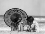 1920s Romantic Couple Looking At One Another Laying Face To Face Under Parasol On Sandy Beach Photographic Print by H. Armstrong Roberts