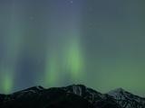 Aurora Borealis over Mountain Range Photographic Print by John Eastcott & Yva Momatiuk