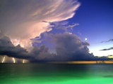 Lighting striking over green and blue water
