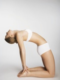 Woman stretching in camel pose Photographic Print by Mario Castello