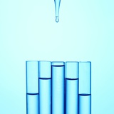 A Glass Pipette Drops Water in to a Series of Staggered Test Tubes or Vials Photographic Print by  TongRo