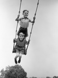 1930s Two Boys Sitting Standing On Playground Swing Photographic Print by H. Armstrong Roberts