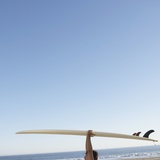 Head and arms of man carrying surf board above head at beach Photographic Print by John Lund