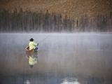 Man fishing on foggy lake Photographic Print by David Stoecklein