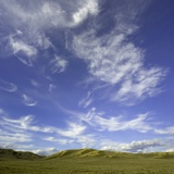 Lofty cumulus and cirrus clouds over sagebrush prairie Photographic Print by John Eastcott &amp; Yva Momatiuk
