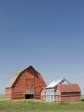 Red Barns in the Middle of a Large Flat Field in the Prairie Land of Southern Saskatchewan, Canada Photographic Print by Rolf Hicker