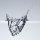 Ice cube splashing in water Photographic Print