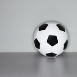Soccer ball next to wall Photographic Print