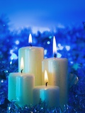 Lighted candle arrangement surrounded by Christmas decorations Photographic Print