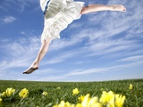 Young woman in park jumping on lawn Photographic Print