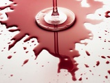 Red wine spilled around glass Photographic Print